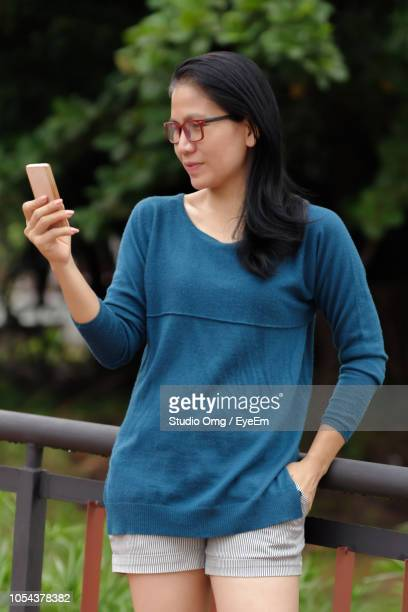 Mature Woman Using Mobile Phone While Leaning On Railing