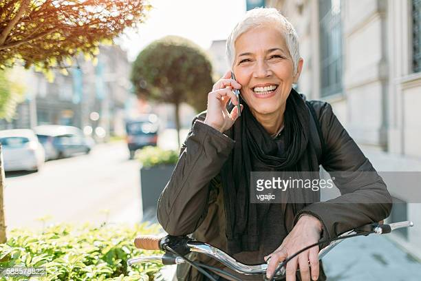 mature woman using phone on her bicycle. - white hair stock photos and pictures