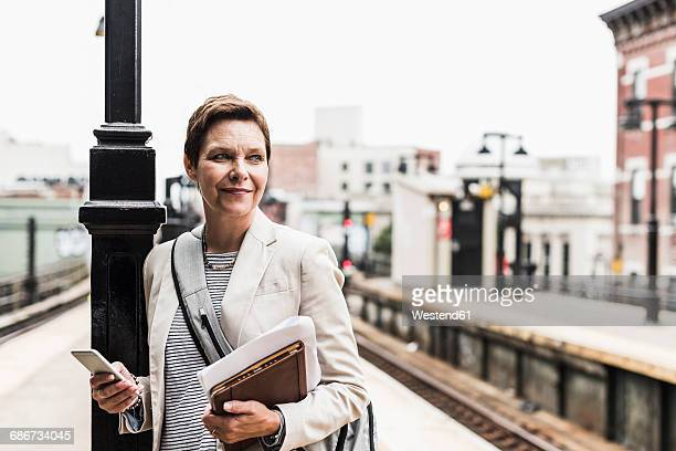 mature woman using smart phone at commuter train station - crossbody bag stock pictures, royalty-free photos & images