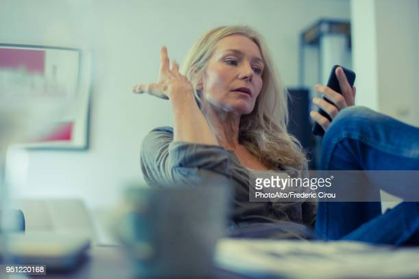 mature woman using smartphone at home - long distance relationship stock pictures, royalty-free photos & images