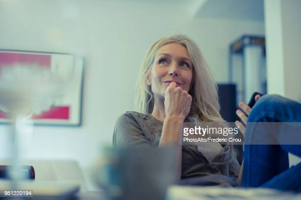 Mature woman using smartphone at home