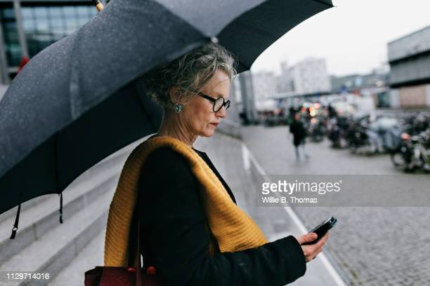 mature woman using smartphone on rainy day - grijs haar stockfoto's en -beelden