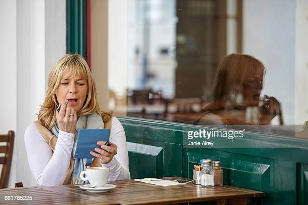 Mature woman using smartphone to apply lipstick at sidewalk cafe table