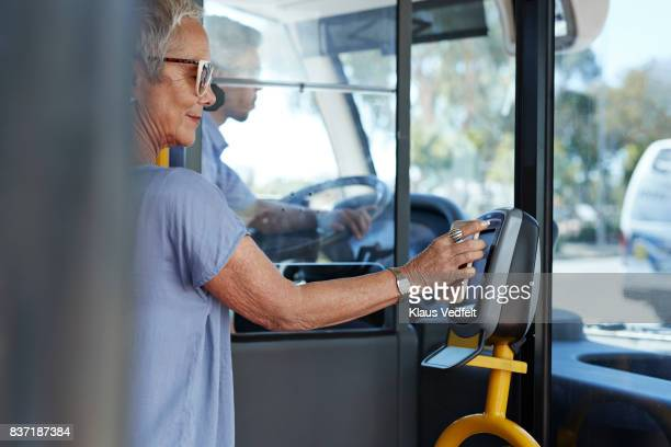 Mature woman using smartphone to pay for public bus ride