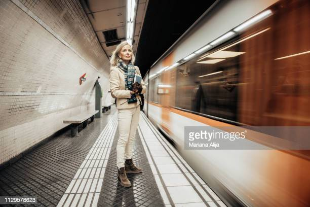 mature woman using subway to get to work - transporte público imagens e fotografias de stock