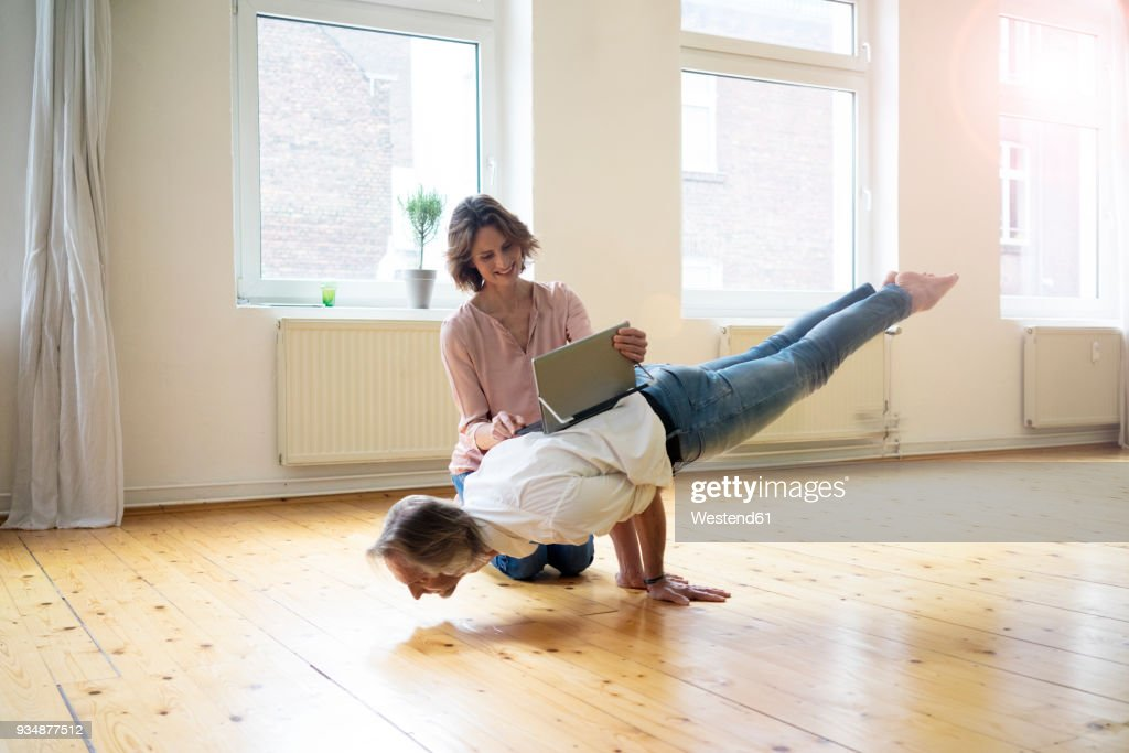 Mature woman using tablet on back of man doing a handstand : Stock Photo