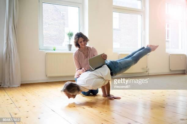mature woman using tablet on back of man doing a handstand - hommes et femmes nus photos et images de collection