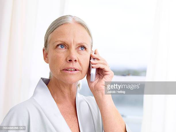 Mature woman using telephone, looking upwards