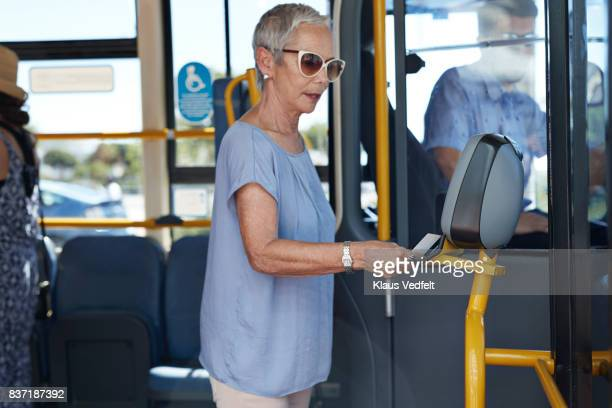 Mature woman using travel card to pay for public bus ride