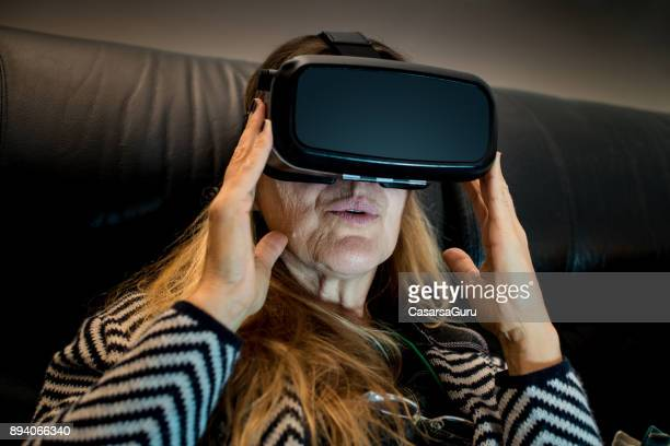 mature woman using virtual reality headset indoors - head mounted display stock photos and pictures