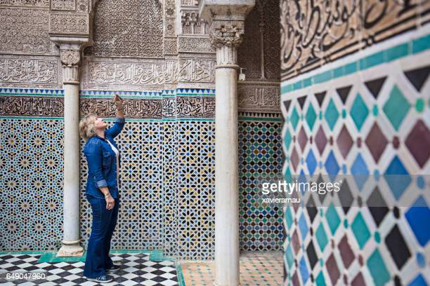 mature woman visiting attarine madrasa in fez - mosaic stock photos and pictures