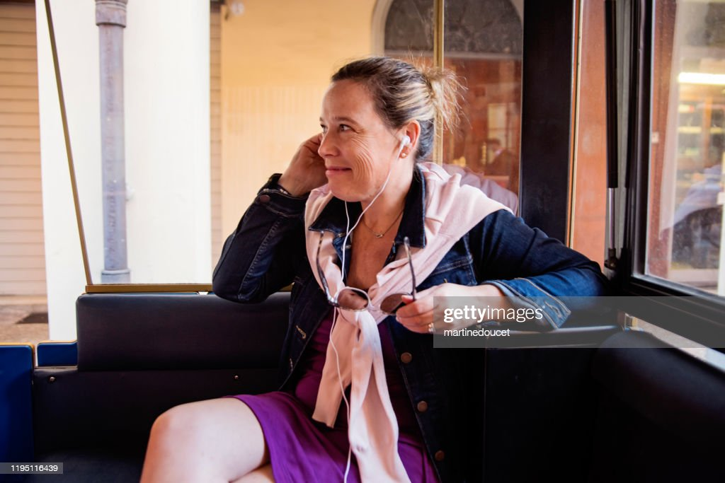 Mature woman visiting the city in tour bus. : Stock Photo
