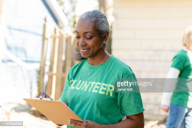 mature woman volunteer with clipboard - volunteer stock pictures, royalty-free photos & images