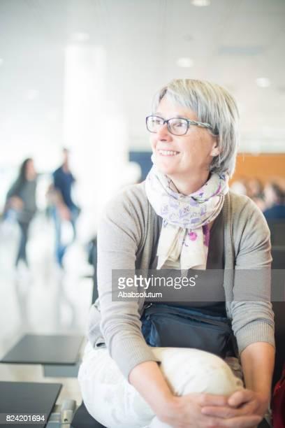 Reife Frau wartet ihr Flug am Flughafen-Lounge, Deutschland