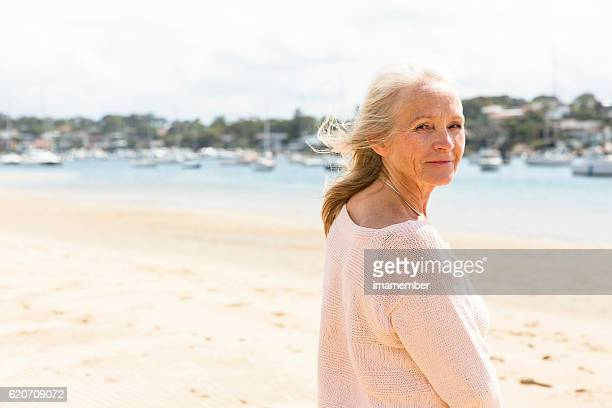 Mature woman waking on the beach in sunshine, copy space