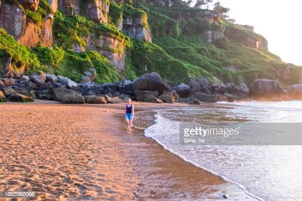 mujer madura caminando a lo largo de la costa - principado de asturias fotografías e imágenes de stock
