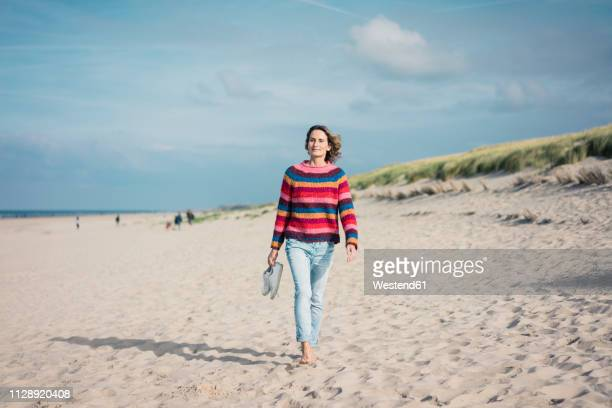 mature woman walking barefoot on the beach - walking stockfoto's en -beelden