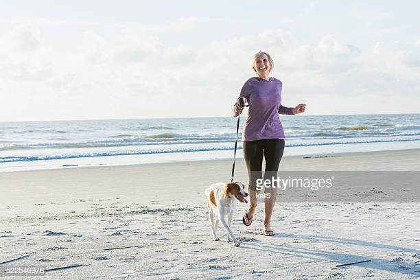 Mature woman walking dog on beach