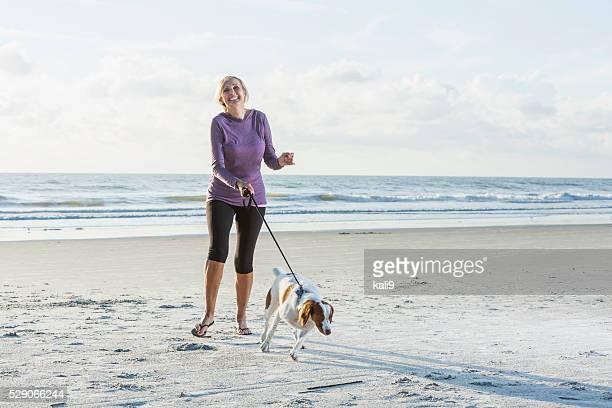 Reife Frau zu Fuß Hund am Strand
