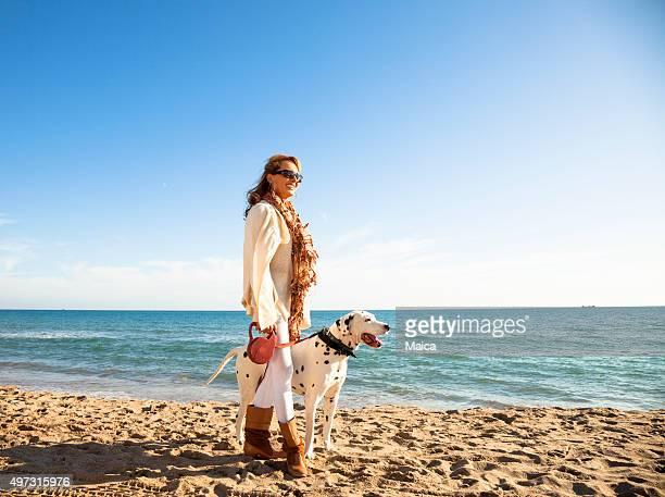 Mujer madura a su dálmata por la playa