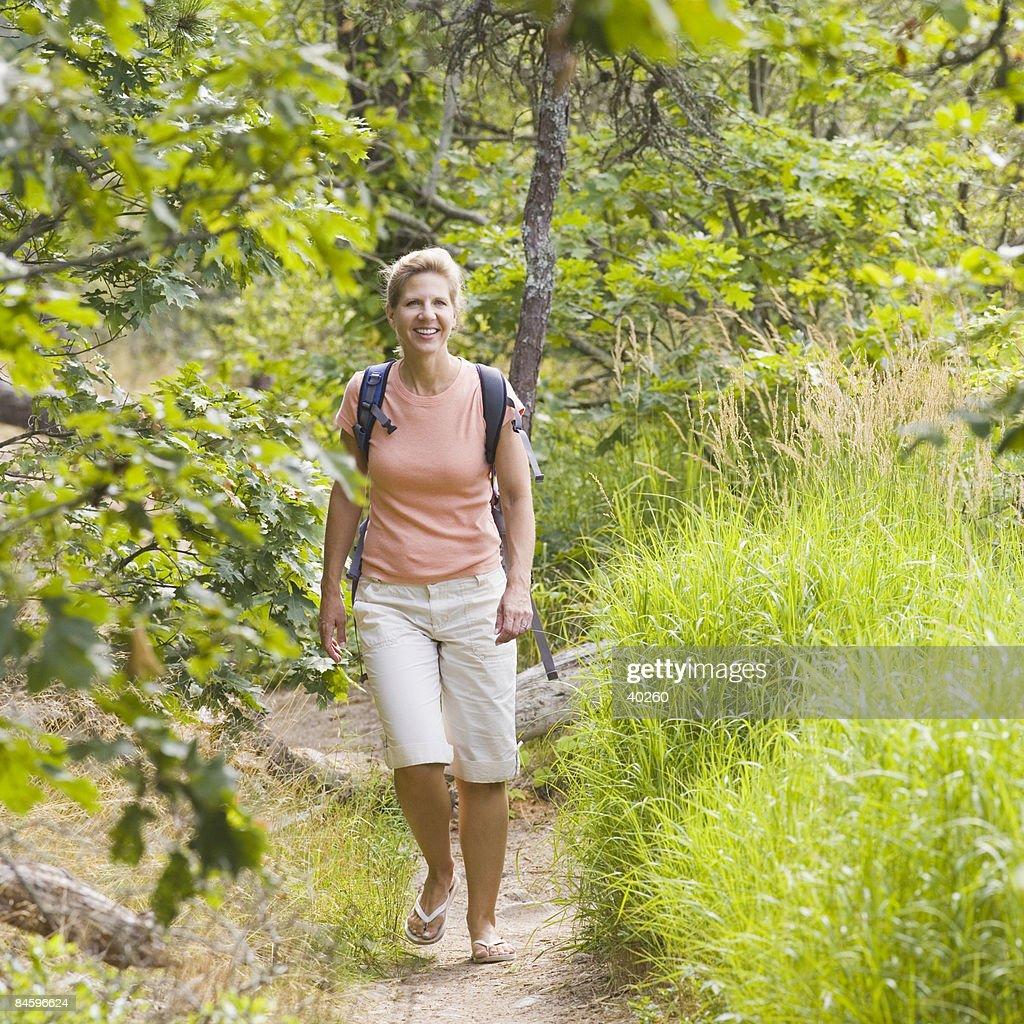 Mature Woman Walking In A Forest And Smiling High-Res