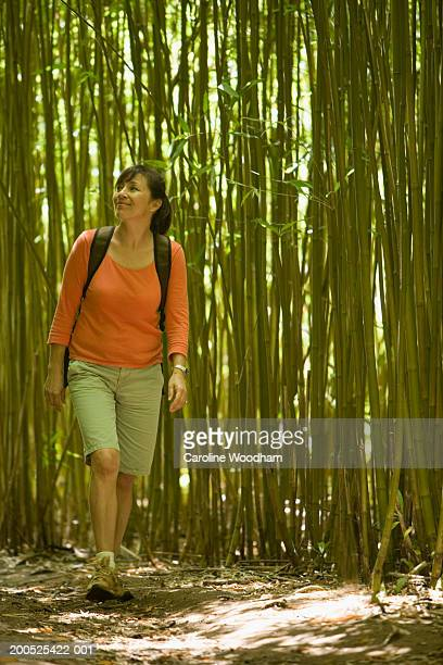 Mature woman walking in bamboo forest