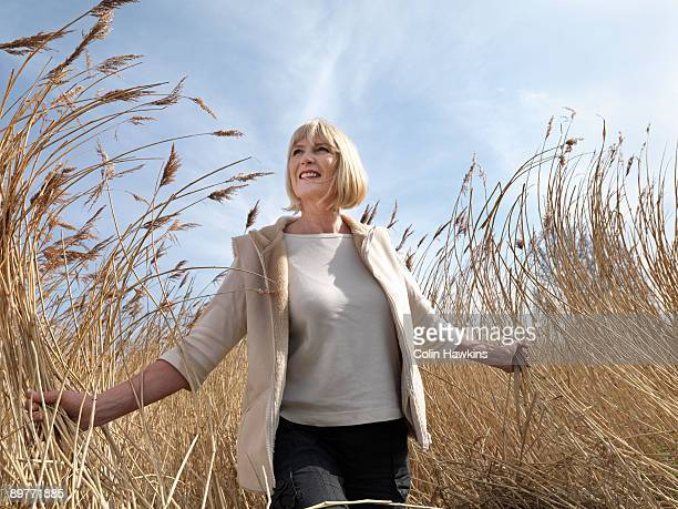 mature woman walking in reeds