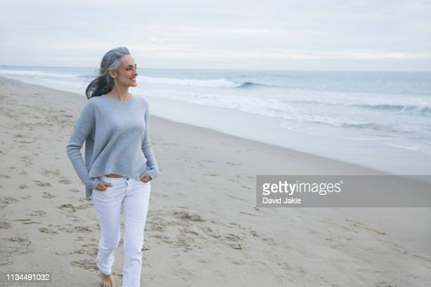 mature woman walking on beach, los angeles, california, usa - gray pants stock pictures, royalty-free photos & images