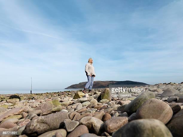 mature woman walking on beach - ポーロック ストックフォトと画像