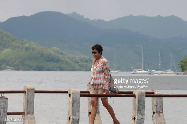 mature woman walking on pier over sea - oppie muharti stock pictures, royalty-free photos & images