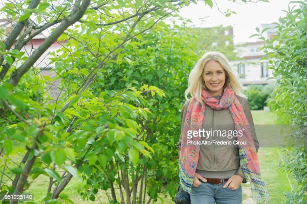 mature woman walking outdoors, smiling, portrait - une seule femme d'âge mûr photos et images de collection