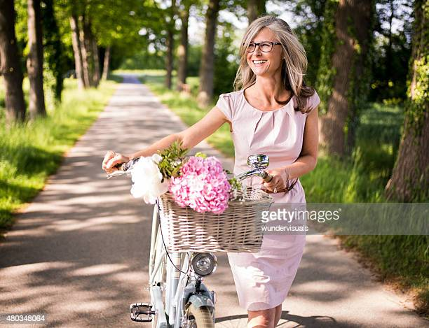 mature woman walking through a park with her classic bicycle - one mature woman only stock pictures, royalty-free photos & images