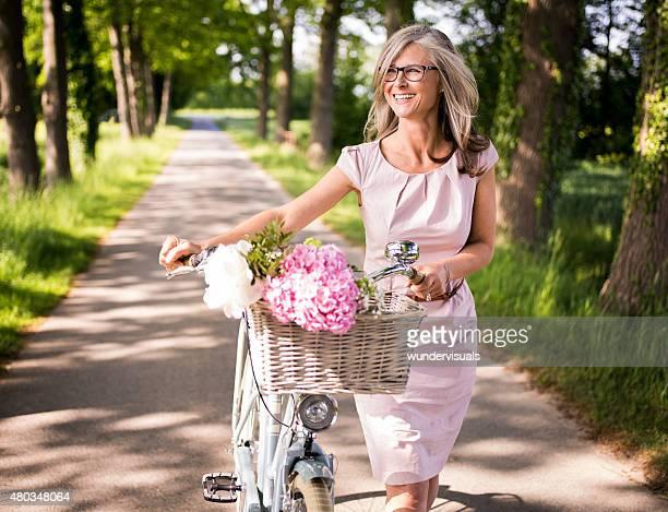 Reife Frau zu Fuß in einem park mit ihren klassischen, Fahrrad