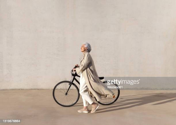 mature woman walking with bicycle on footpath during sunny day - elegance stock pictures, royalty-free photos & images