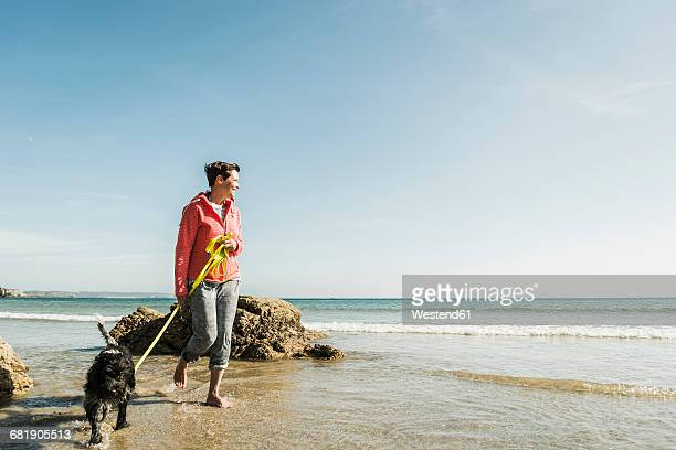 Mature woman walking with dog at the sea