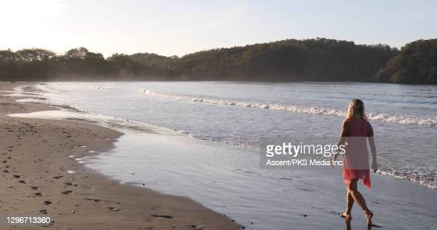 mature woman walks along beach, into sunrise - early retirement stock pictures, royalty-free photos & images