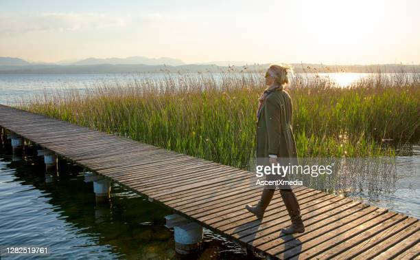 mature woman walks along wooden boardwalk at dawn - pier stock pictures, royalty-free photos & images