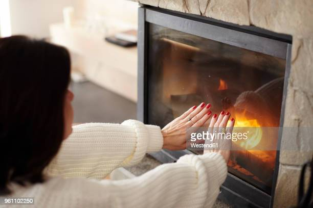 mature woman warming her hands at the fireplace - 暖炉の火 ストックフォトと画像