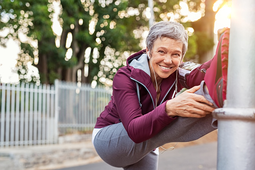 Mature woman warming up before jogging 1044161320