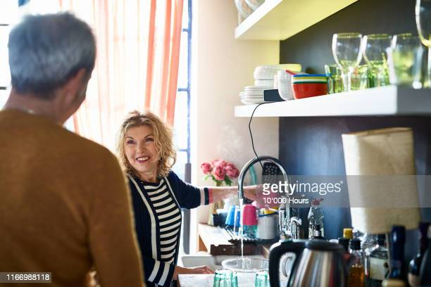 mature woman washing dishes at sink and smiling at husband - couples showering stock pictures, royalty-free photos & images