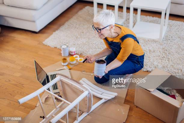 mature woman watching diy tutorials and painting a chair - tutorial stock pictures, royalty-free photos & images
