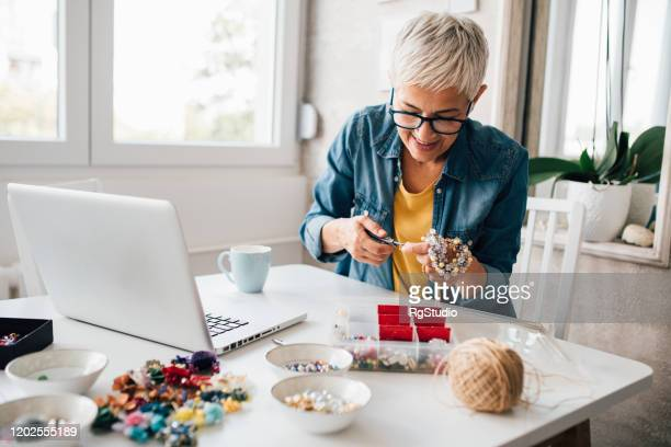 mature woman watching tutorials for making jewelry - hobbies stock pictures, royalty-free photos & images