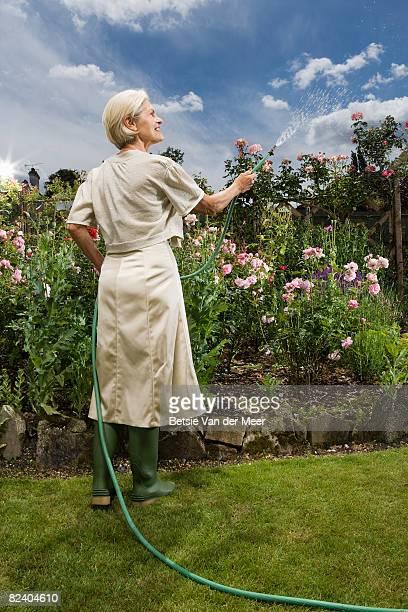mature woman watering plants in garden.