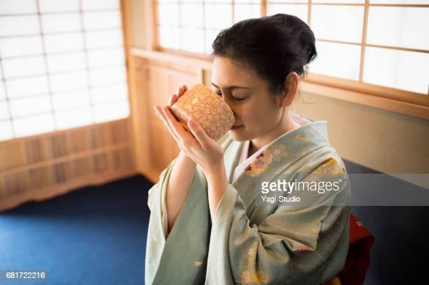 Mature woman wearing a kimon enjoy tea at a Japanese tea room