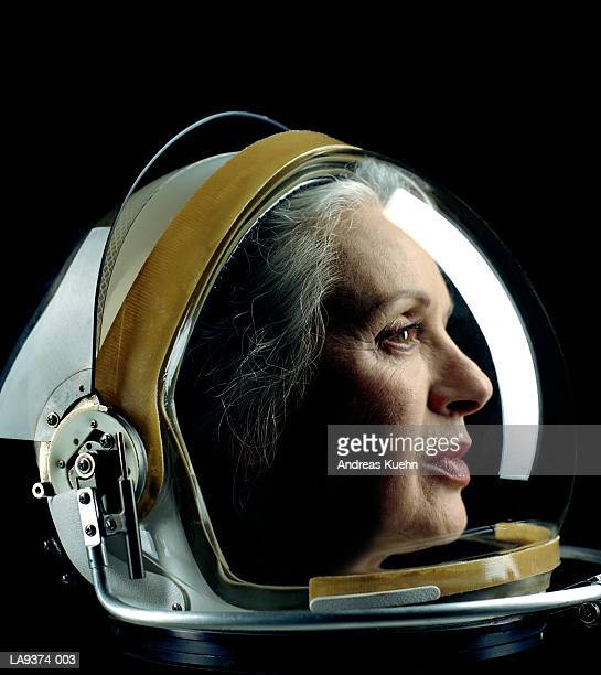 Mature woman wearing astronaut helmet