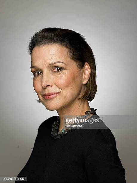 femme d'âge mûr portant haut noir et collier, portrait - femme 50 ans brune photos et images de collection