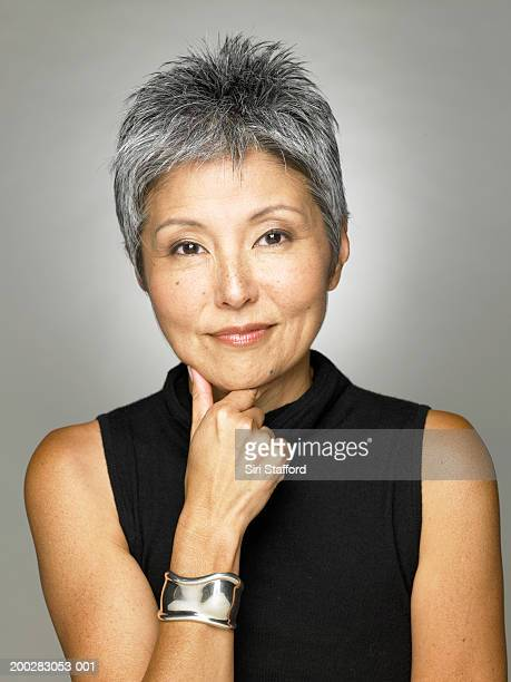 mature woman wearing black top, portrait - asian 50 to 55 years old woman stock photos and pictures