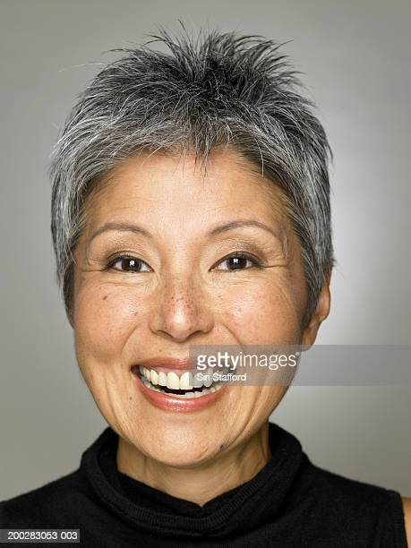 mature woman wearing black top, smiling - asian 50 to 55 years old woman stock photos and pictures