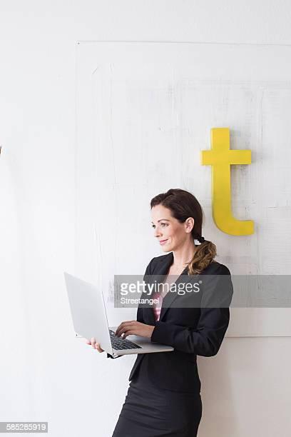 mature woman wearing business attire standing using laptop - letra t imagens e fotografias de stock