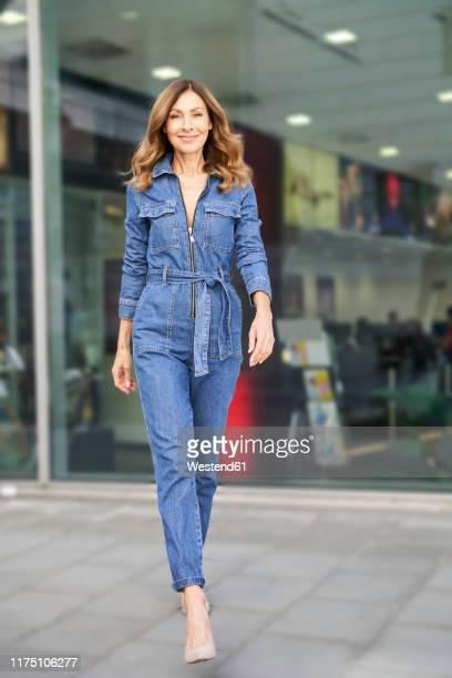 mature woman wearing denim jumpsuit - hoge hakken stockfoto's en -beelden